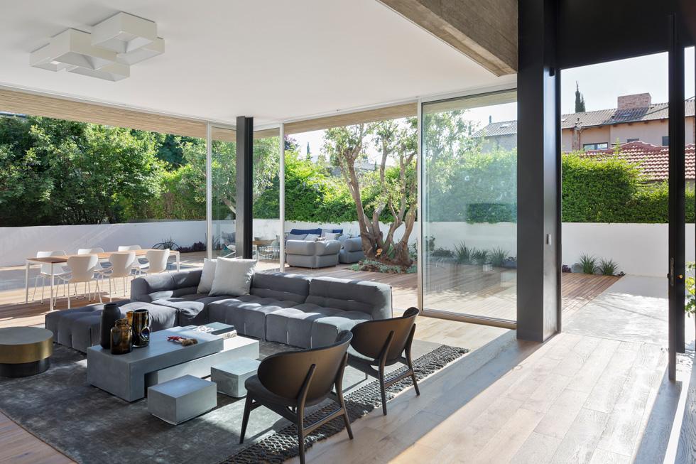 שני קירות זכוכית נפתחים אל חצר גדולה המחופה בדק, כך שהיא נראית כהמשכו של הסלון. שתי שכבות של וילונות מאפשרות החשכה (צילום : שי אפשטיין)