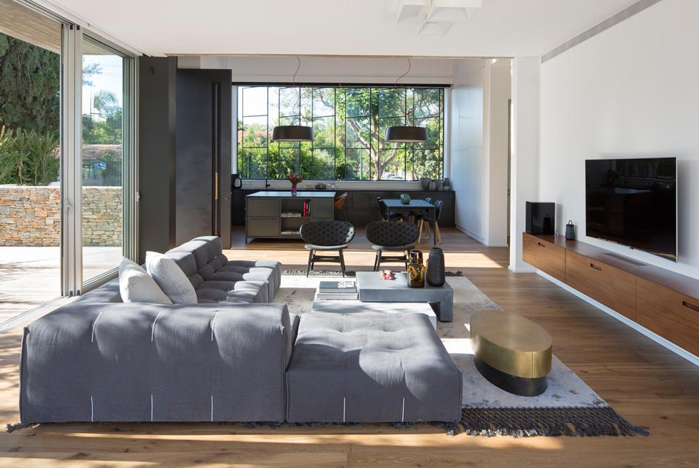 בסלון גוונים אפורים וחומים-זהובים. ספה פינתית גדולה על רצפת עץ אלון, שידה תואמת תלויה על הקיר מתחת למסך, ובמרכז קוביות-שולחנות (צילום : שי אפשטיין)