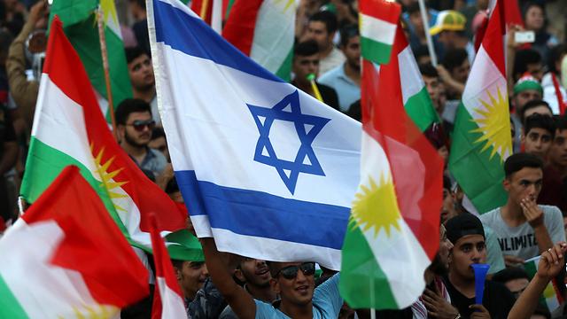 Iraqi Kurds fly an Israeli flag and Kurdish flags during an independence rally (Photo: AFP)