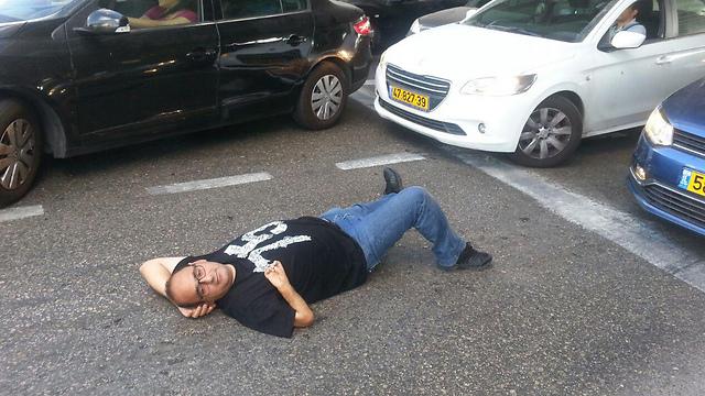 Protestor lying on road to block traffic (Photo: Amir Alon) (Photo: Amir Alon)