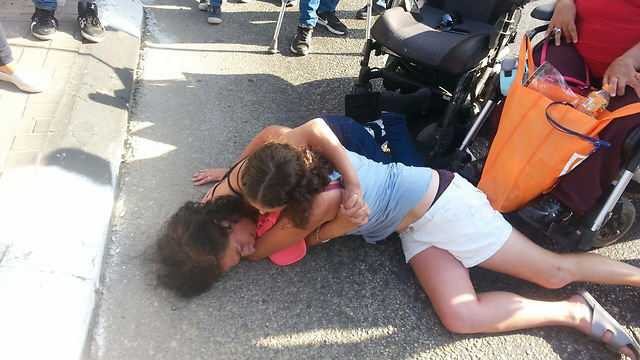 Cuffed protestor lying on ground and covered by friend (Photo: Amir Alon) (Photo: Amir Alon)