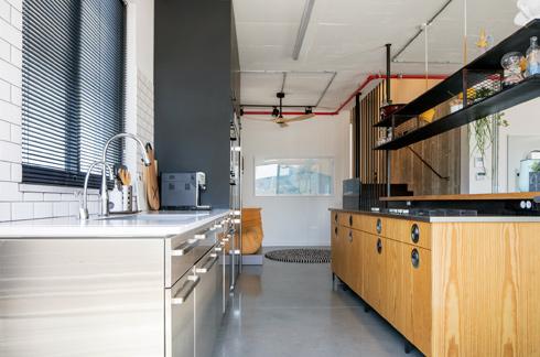 ארונות המטבח בסגנון תעשייתי, ובעומק התמונה פינת הטלוויזיה (צילום: אביעד בר-נס)