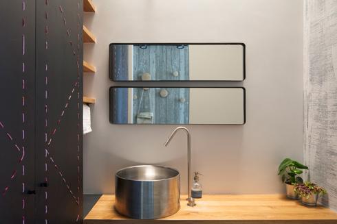 בשירותי האורחים כיור שעוצב מגליל נירוסטה וארון עם דלתות פח מחורר. מעל מאיר חלון סקיי-לייט (צילום: אביעד בר-נס)