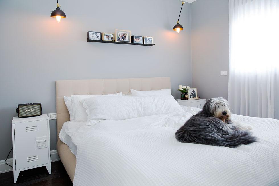 חדר השינה של ליהי הוד וגיא קרני, עם הדיירת הקבועה לוסי על המיטה (צילום: ענבל מרמרי)