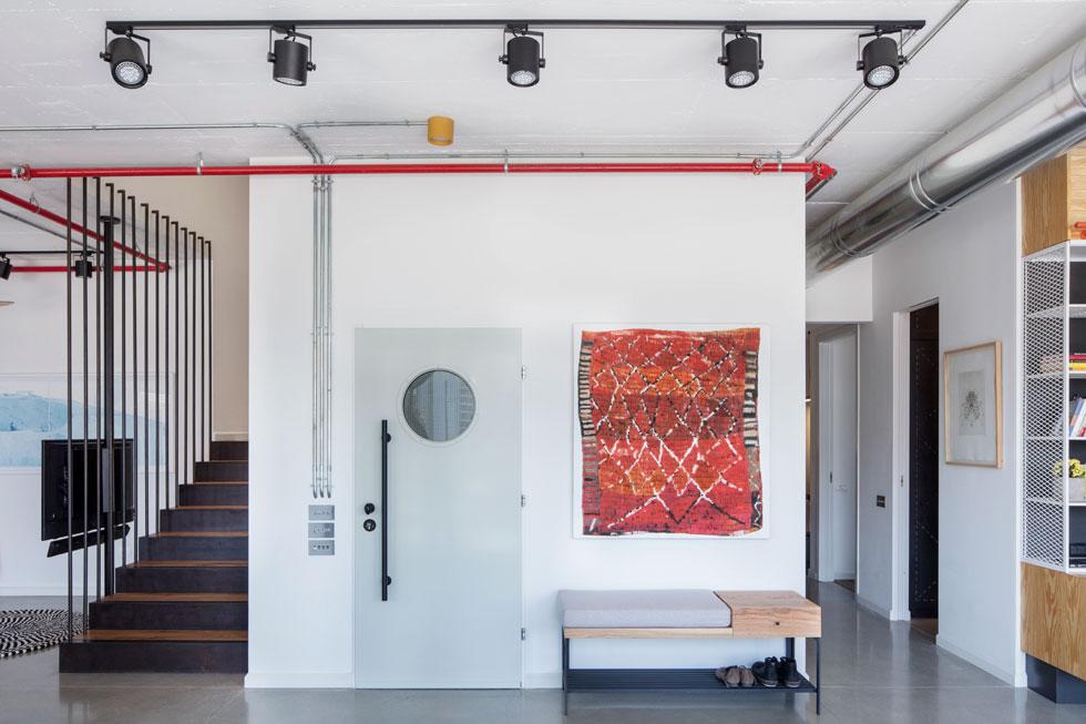 לצד דלת הכניסה ספסל שעוצב במיוחד. התשתיות חשופות: צינורות הספרינקלרים אדומים, צינורות החשמל אפורים. על הקיר ציור של טל ירושלמי  (צילום: אביעד בר-נס)