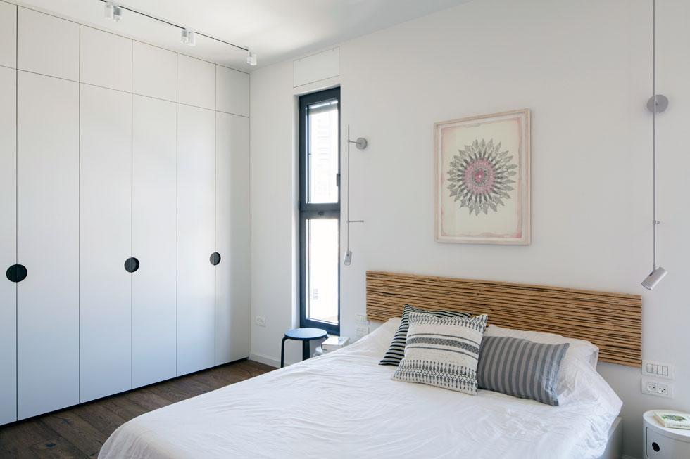 בחדר ההורים ארונות קיר לבנים עם מגרעות משובצות פח שחור. על הקיר בגב המיטה עבודה של יעל בלבן   (צילום: אביעד בר-נס)