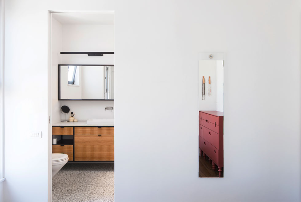 בחדר הרחצה של ההורים ארון כיור שהוזמן מבמבוק. במראה נשקפת השידה שמול המיטה הזוגית, שנצבעה בטרקוטה   (צילום: אביעד בר-נס)