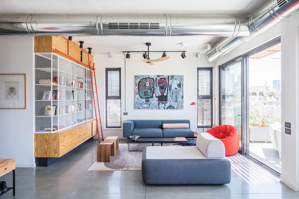 הספרייה בסלון עוצבה במיוחד לדירה. על הקיר הניצב לה ציור של אילנה גל, והטלוויזיה בפינה אחרת של החלל, לצד המטבח (צילום: אביעד בר-נס)