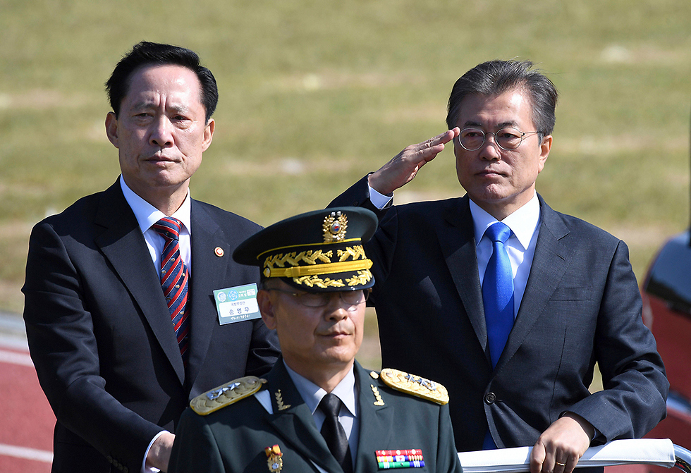 הנשיא מון (מימין) ושר ההגנה סונג יאנג מו (משמאל) מצדיעים לחיילים (צילום: AP)