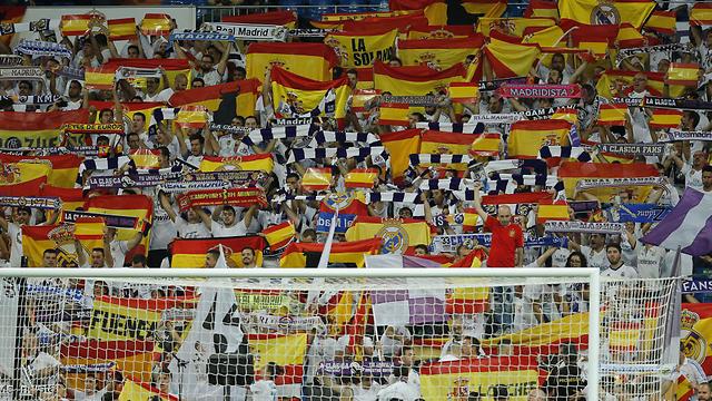 אוהדי ריאל מדריד מקניטים את היריבה המושבעת ברצלונה, הנמצאת בקטלוניה, באמצעות הנפת דגלי ספרד (צילום: AP)