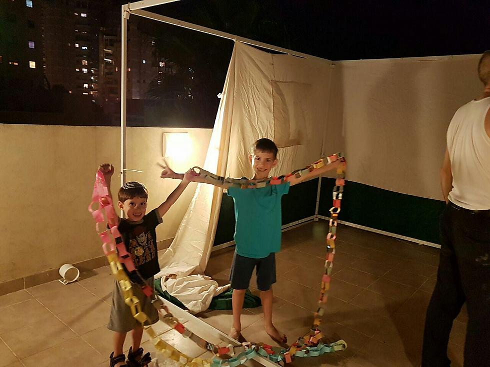 אלישע ומלאכי מאן מגבעת שמואל בונים סוכה עם אבא (צילום: רויטל נגלר-מאן)