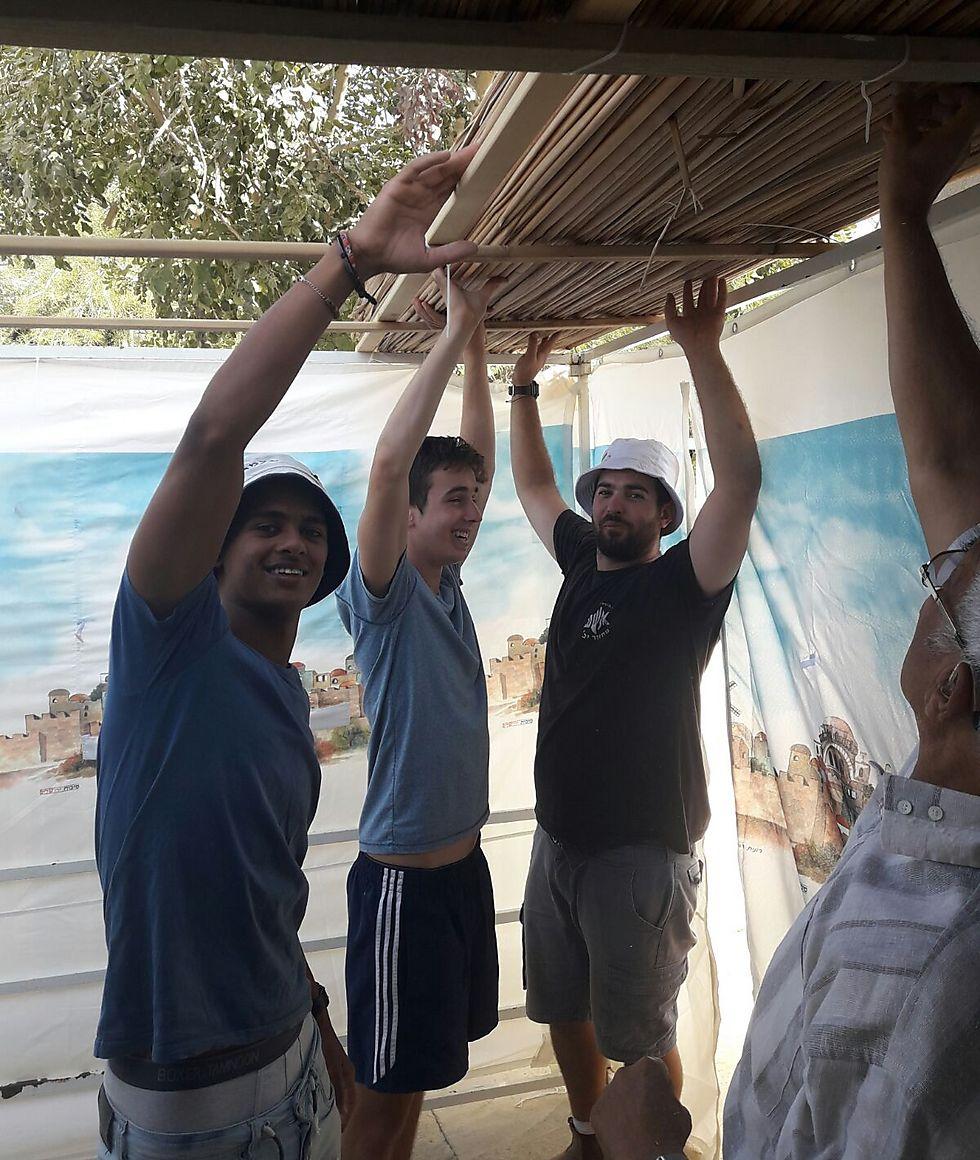 יצחק פרש, נבו ביטון ואביחי אלמו, חניכי OU ישראל, מתנדבים בהקמת הסוכה של משפחת בן שימול (צילום: אורן סממה)
