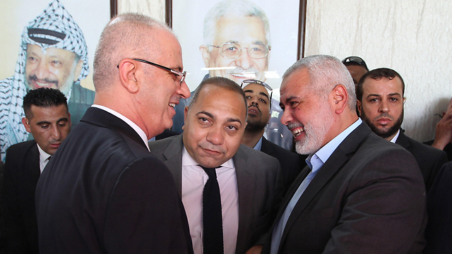 Palestinian Prime Minister Rami Hamdallah (L) shakes hands with Hamas leader Ismail Haniyeh in Gaza City. No need to explain who the dangerous bride is    (Photo: AFP)
