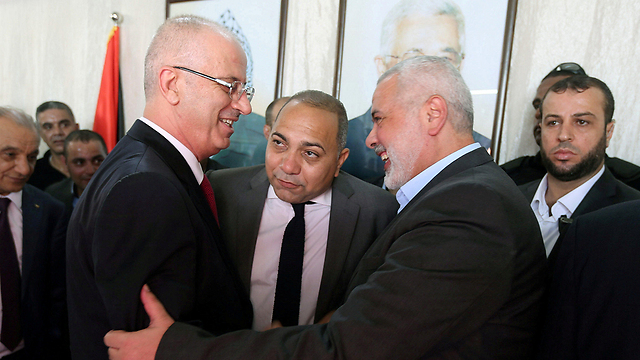 Rami Hamdallah and political leader of Hamas Ismail Haniyeh shake hands as Hamas transfers administrative power to the PA (Photo: Reuters) (Photo: Reuters)