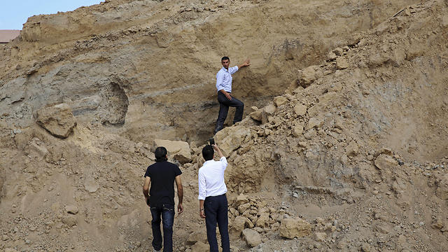 Sorosh-Wali takes photos while Fadel al-A'utul, a worker with French excavation mission, explains to him the damage at Tel Es-Sakan hill (Photo: AP)