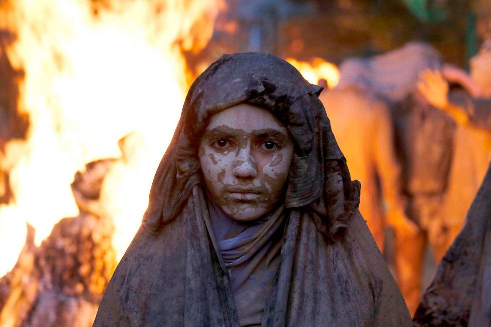 מוסלמית שיעית מרוחה בבוץ בטקס יום העשורא בחוראמאבד, איראן (צילום: AFP)