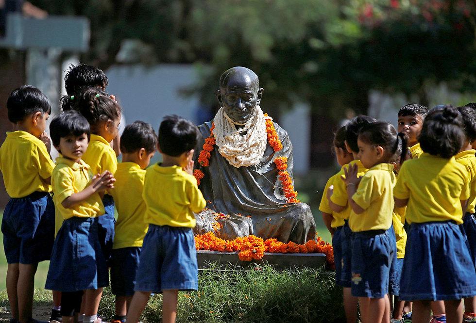 תלמידי בית ספר מתפללים לפסל של מהטמה גנדי לציון 148 שנה להולדתו. אחמדאבד, הודו (צילום: רויטרס)