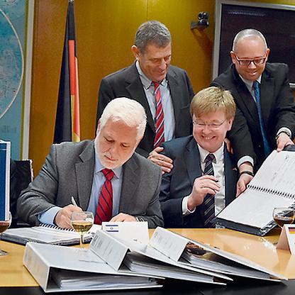גנור (עומד במרכז) בטקס חתימת ההסכם על ספינות השטח