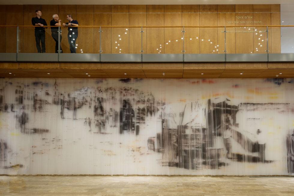 עבודה גדולה של האמן יזהר פטקין נמצאת במבואה: וילון ארוך ועליו דימויים בהשראת ארכיון התזמורת (צילום: גדעון לוין)