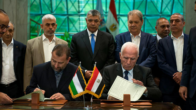 Sinwar watches as senior Fatah official Azzam al-Ahmad (R) and Hamas deputy politburo chief Saleh al-Arouri sign a reconciliation deal in Cairo last Thursday  (Photo: EPA)