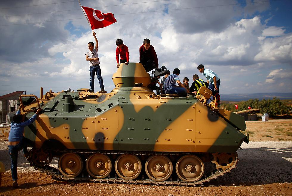 ילדים על משוריינים של צבא טורקיה בעת שחצו את הגבול לסוריה (צילום: רויטרס)
