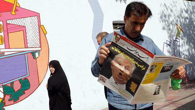 Iranian reads about Trump's speech in local paper (Photo: EPA)