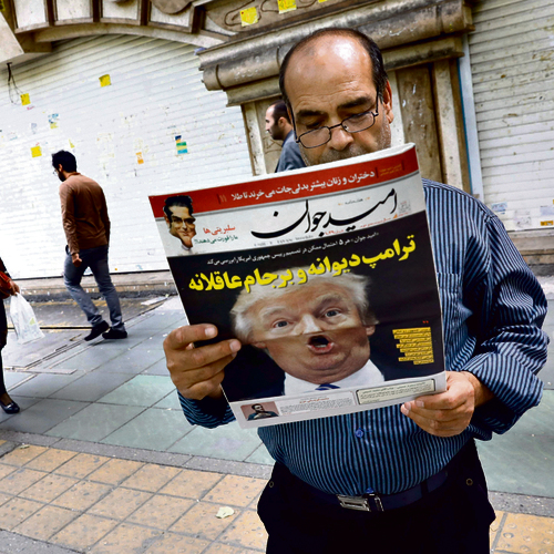 An Iranian man reading a newspaper mocking US president as 'Crazy Trump' following Friday's speech   (Photo: AFP)
