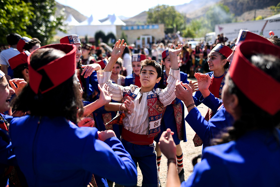 ילדים בתלבושות מסורתיות רוקדים במהלך פסטיבל היין בעיר ארני, שנמצאת במרחק 120 קילומטרים מהבירה ירוואן (צילום: AFP) (צילום: AFP)
