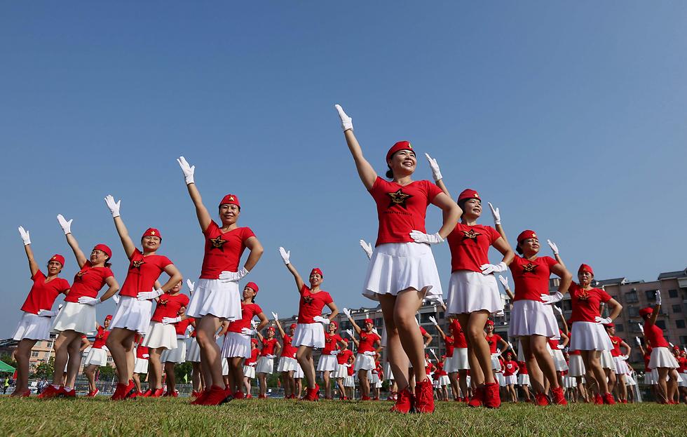 מופע ריקוד במחוז גואנגשי בסין לקראת פתיחת קונגרס המפלגה הקומוניסטית השנתי (צילום: AFP) (צילום: AFP)