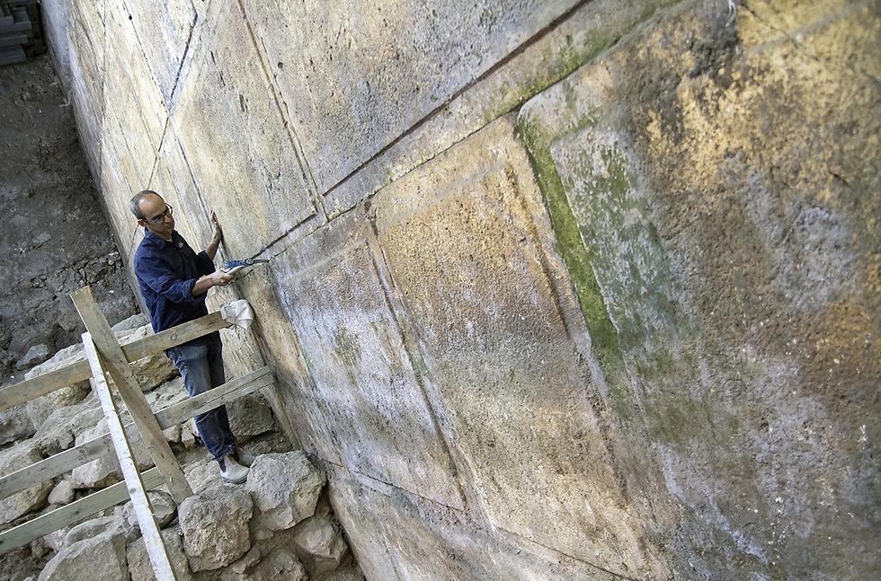 """ארכיאולוג רשות העתיקות ד""""ר ג'ו עוזיאל ליד אבני הכותל שנחשפו בחפירה (צילום: יניב ברמן, באדיבות רשות העתיקות) (צילום: יניב ברמן, באדיבות רשות העתיקות)"""