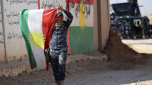 A member of the Iraqi forces holds up a Kurdish flag (Photo: AFP)