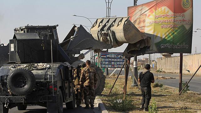 Iraqi forces use an excavator to damage a poster of Iraqi Kurdish president Massud Barzani (Photo: AFP)