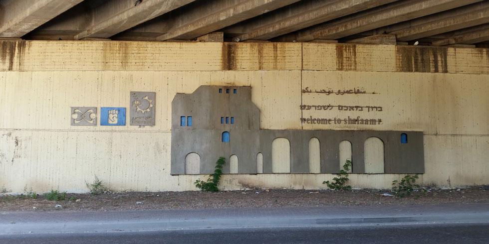 תבליט בטון מתחת לגשר בכניסה לשפרעם. מקרה נדיר של שלט בשלוש שפות (צילום: אורי זקהם)
