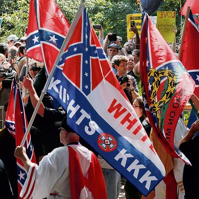 """מפגין עם דגל קו־קלוקס־קלאן. """"לא לבלום את התופעה. לחסל אותה"""""""