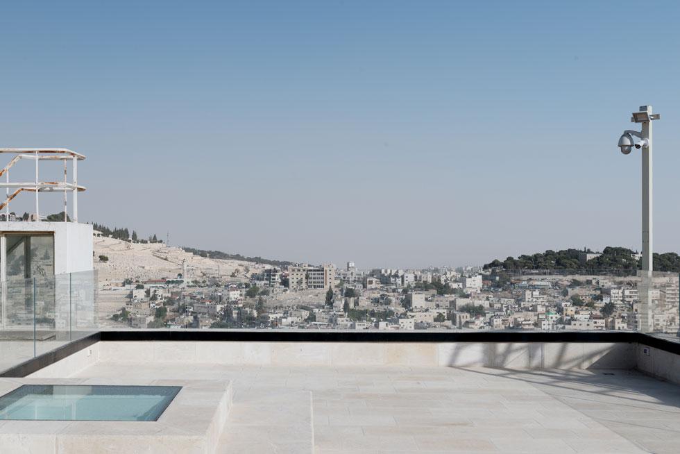 נופי ירושלים נשקפים ממרפסת הגג. משמאל: הפתח הריבועי המזוגג שמחדיר אור טבעי לפינת האוכל שמתחתיו  (צילום: גדעון לוין)