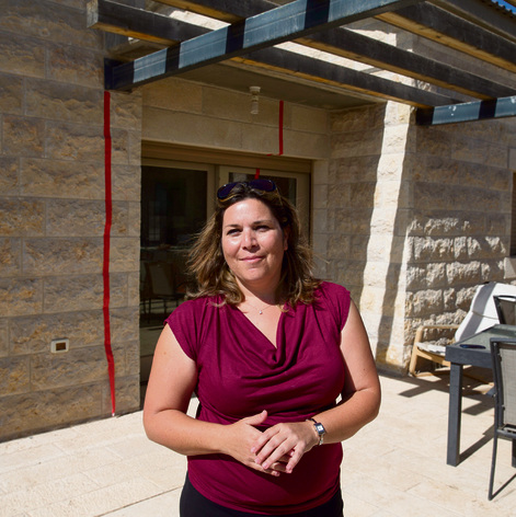 Rachel Bulvik outside her house. Red lines mark 'extension' built on Palestinian land  (Photo: Amit Shabi)