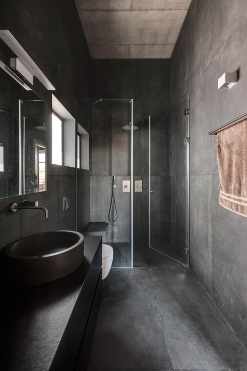 אפילו חדרי הרחצה עשויים בטון. בעל הבית מסביר את יתרונותיו: הוא לא מתלכלך ומתקלף כמו טיח  (צילום: עודד סמדר)