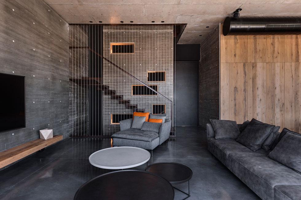 מבט מהסלון לכיוון הדלת וגרם המדרגות הפיסולי. על קיר הבטון תלוי רק מסך טלוויזיה שחור (צילום: עודד סמדר)