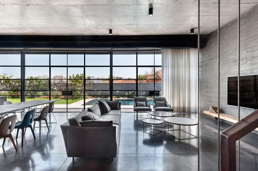 הרהיטים נבחרו כולם בגווני אפור-שחור-לבן, וקירות הזכוכית לכל אורך החזית הצפונית מכניסים פנימה אור טבעי נעים, ואת צבעי הבריכה והצמחייה (צילום: עודד סמדר)