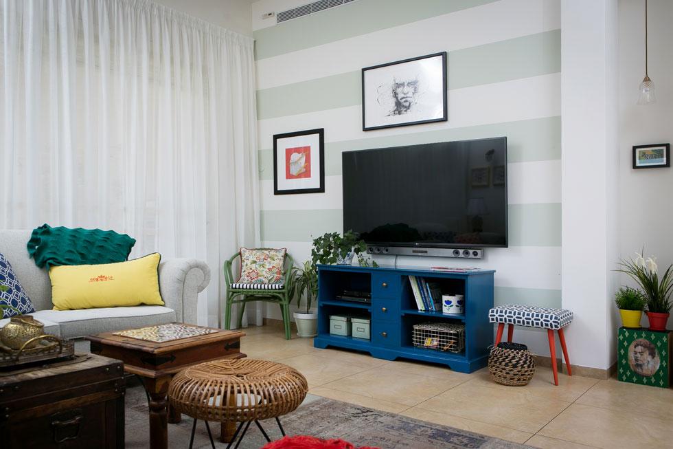 אצל רוני עשת זה לא טפט אלא קיר שנצבע בדוגמת פסים, כריות ססגוניות ושידת טלוויזיה שקיבלה גוון כחול עמוק (צילום: שירן כרמל)
