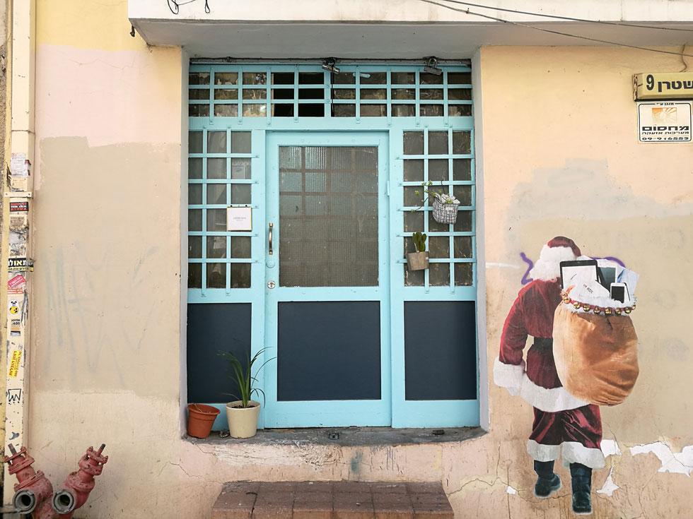 מאחורי דלת הטורקיז ברחוב שטרן 9 בפלורנטין יש סיפור משפחתי שמתחיל ב-1934. (לסנטה קלאוס שלצדה אחראי אמן הרחוב TAG#)  (צילום: ציפה קמפינסקי)