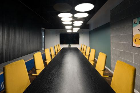 חדר הישיבות המרכזי בקומה 15. קיר בלוקים חשוף וכסאות מרופדים (צילום: גדעון לוין)
