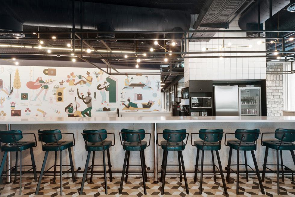 הקפיטריה בקומה 13 מוגדרת באמצעות ריצוף מעוינים בגווני חום. הבר עשוי מבלוקים חשופים, ומעליו גופי תאורה דקורטיביים מפליז. כסאות הבר עשויים ברזל ומרופדים בירוק כהה. ציור הקיר הגדול והפסטלי הוא של עינת צרפתי (צילום: גדעון לוין)