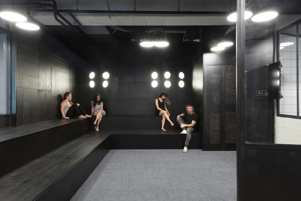 טריבונות עץ מושחר בקומה 15 מיועדות למפגשי הצוותים השונים העובדים בקומה. יחד עם התאורה הטכנית נוצרת אווירה של מאחורי הקלעים (צילום: גדעון לוין)