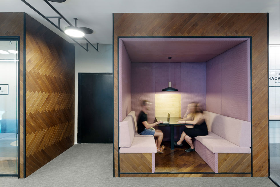 תא מפגש (בוט) בקומה 13 מחופה מבחוץ בפרקט אלון בדוגמת אדרת דג ומרופד מבפנים - קירות וספסלים - בטקסטיל ורוד. התאורה חמה ואינטימית (צילום: גדעון לוין)