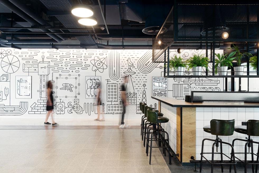 הקפיטריה המרכזית בקומה 15. הדלפקים עשויים עץ ומחופים באריחי קרמיקה לבנים, פשוטים. על הרצפה פוגשים אריחים מלבניים שחורים אריחי טראצו ו''שביל'' קומתי שעשוי מפרקט אלון. על הקיר איור גדול של אלון בונדר (צילום: גדעון לוין)