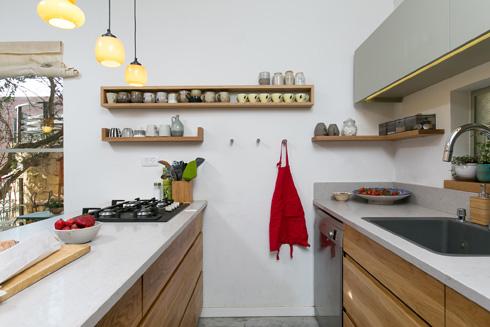 המטבח קטן ופונקציונלי. הארונות והאי עשויים מאלון בהיר   (צילום: שירן כרמל)