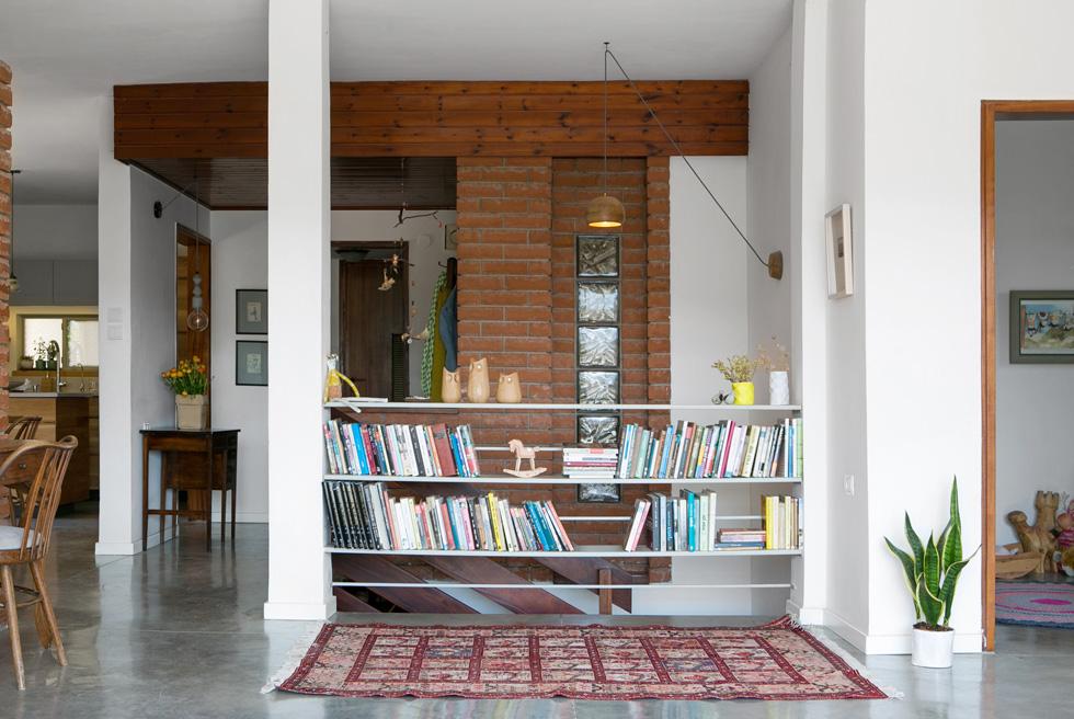 """מבואת הכניסה המקורית, עם קיר הלבנים האדומות וחיפוי המהגוני, נשמרה. גם משקוף המעבר לחדרה של הבת הצעירה (מימין) נשאר עם המהגוני המקורי. """"היה לנו מאוד חשוב"""", אומרת בעלת הבית, אדריכלית נוף במקצועה, """"לשמור על עקרונות התכנון ועל ההיסטוריה והסיפור של הבית'' (צילום: שירן כרמל)"""