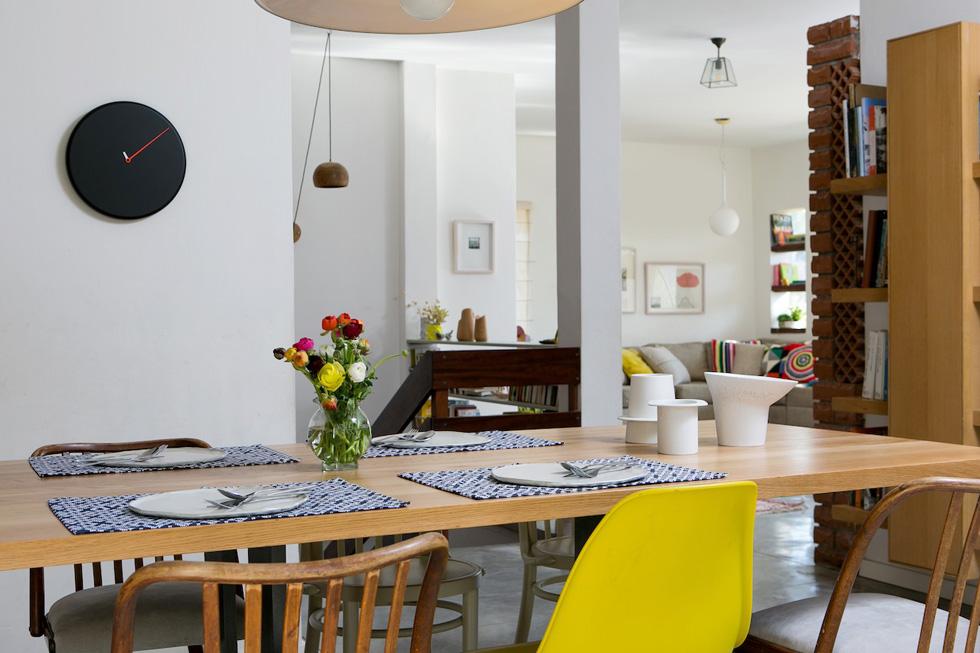 """שולחן האוכל המשפחתי עשוי מאלון טבעי. הכיסאות, שחלקם נשמרו מעזבונה של ויקי בן ציוני, חודשו. """"שולחן האוכל הוא הכי מרכזי, פה כולם יושבים ומתארחים"""". קומת המרתף, שהייתה סגורה שנים, נפתחה מחדש, ואליה עברו שני הבנים הגדולים יותר (צילום: שירן כרמל)"""