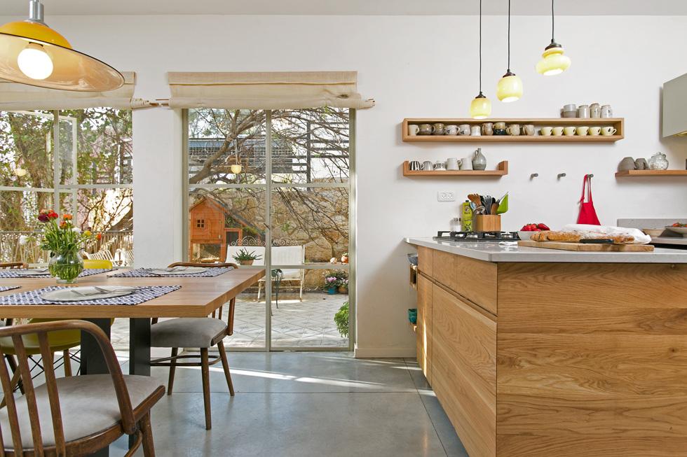 """""""שולחן האוכל ,יחד עם האי ושטחו הקטן של המטבח הפכו להיות אזור מאוד אינטימי ונעים בבית"""". החצר הקטנה שבהמשך לפינת האוכל מרוצפת אריחי בטון ישנים (צילום: שירן כרמל)"""